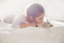 Portrait of a beautiful little girl, lies on a clean, white bed with a white British cat.
