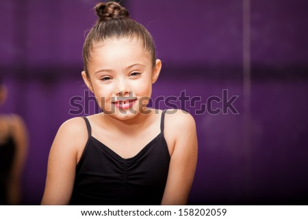 Portrait of a beautiful little girl wearing a ballet outfit and smiling in a dance studio