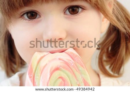Portrait of a beautiful little girl with a big  swirl lollipop