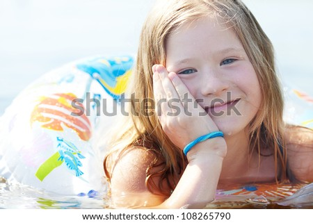portrait of a beautiful little girl with a color lifebuoy