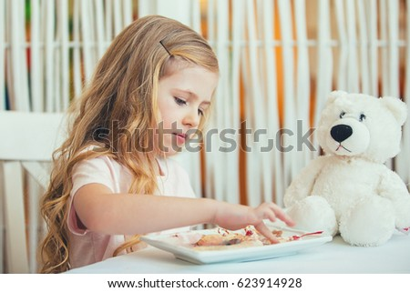 Portrait of a beautiful little girl with a Teddy bear in a cafe eating a delicious ice cream .Happy moments of childhood Zdjęcia stock ©