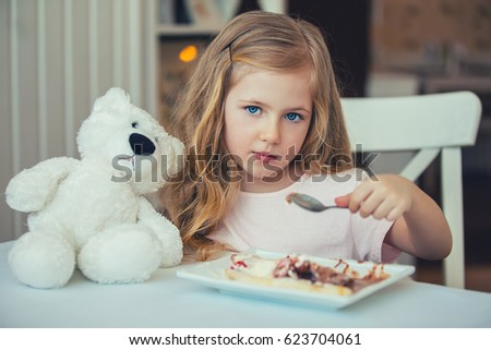 Portrait of a beautiful little girl with a Teddy bear in a cafe eating ice cream .Happy moments of childhood Zdjęcia stock ©
