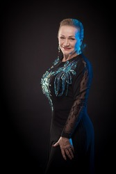 Portrait of a beautiful mature woman in a theatrical costume with shiny decorations posing on a black background