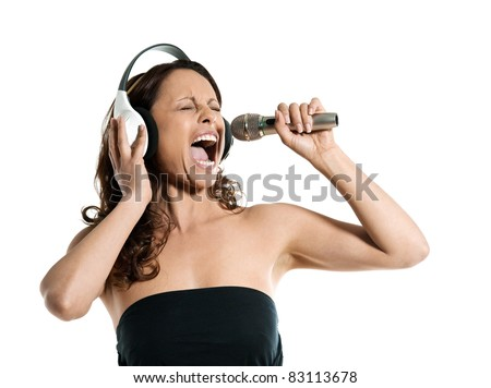 Portrait of a beautiful mature woman singing into microphone with headphones in studio isolated on white background