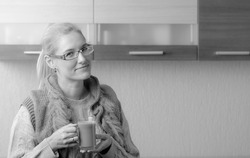 Portrait of a beautiful mid-age woman in glasses with a cup of coffee. Attractive and happy blonde in sweater drinks a latte.
