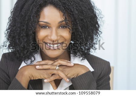 Portrait of a beautiful middle aged African American woman or businesswoman sitting relaxing & smiling