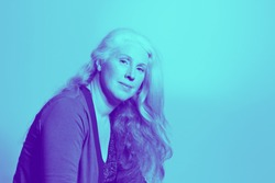 Portrait of a beautiful middle aged woman with long wavy hair in trendy duotone effect, copy space.