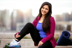 Portrait of a beautiful mixed ethnicity brunette woman in sportswear, sitting relaxed after a morning yoga workout with city skyline in the background