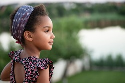 Portrait of a beautiful mixed race kid on a landscape background. Beautiful profile. Soft light. Afro hair. The child looks to the right.  Concept of childhood, travel, dreams. Copy space. Horizontal.