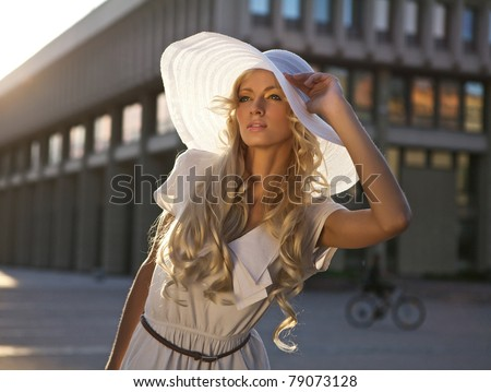 Portrait of a beautiful model in white retro hat. Street fashion photo. - stock photo