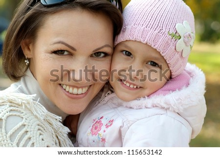 portrait of a beautiful mother and a little girl in the autumn