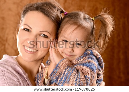portrait of a beautiful mother and daughter on a brown