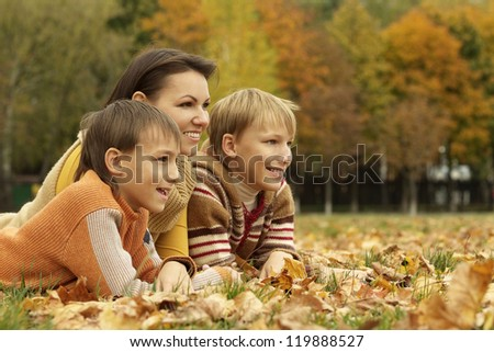 portrait of a beautiful mother and her children are in the autumn park