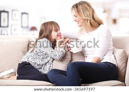 Portrait of a beautiful mother and her little girl sitting at home and sharing a happy moment together. Blond mom holding in her hand a cup of tea.