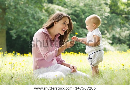 Portrait of a beautiful mother with baby playing in the park