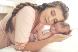 Portrait of a beautiful mother, with her nursing baby. High quality photo.