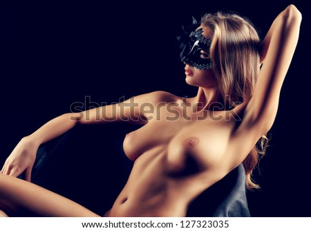 Portrait of a beautiful naked woman in carnival mask posing over black background.