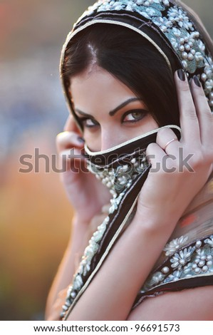 Portrait of a beautiful oriental  woman covered with a colorful veil