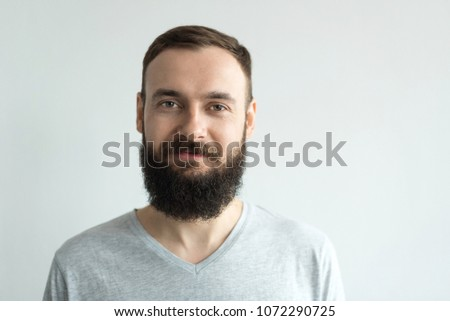 Portrait of a beautiful real hipster man with a full face of a beard and mustache on a light background in a barber shop in a gray shirt #1072290725