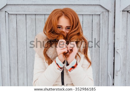Portrait of a beautiful red hair young woman in warm clothes outdoor on the grey wooden background. Girl shows different emotions.