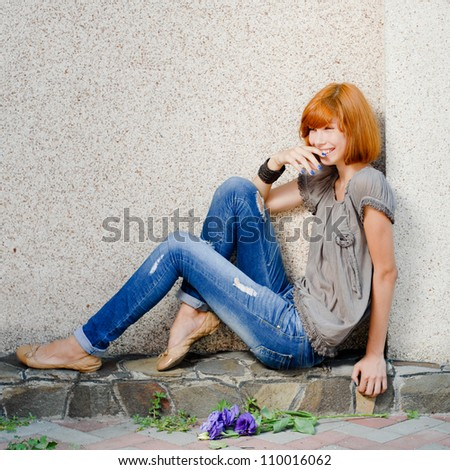 portrait of a beautiful red hair young woman sitting near wall and laughing happilly with chinese rose on the ground