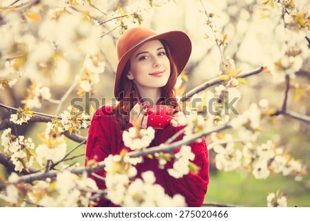 Portrait of a beautiful redhead women in red sweater and hat with cup in blossom apple tree garden in spring time on sunset.