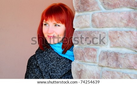 Portrait of a beautiful redheaded young woman against a wall.