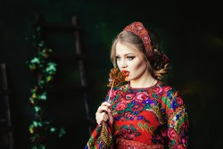 Portrait of a beautiful Russian girl in a kokoshnik and traditional dress. She is holding a cockerel (lollipop) on a stick. Russian folk, retro, ethno. Pavlovo Posad shawl. Selective focus photo