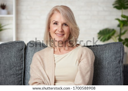 Portrait of a beautiful senior blonde woman smiling at home. Old granny