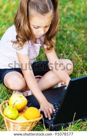 portrait of a beautiful, serious girl (child) sitting on the grass with laptop and basket of fruit (apples, pears, oranges)