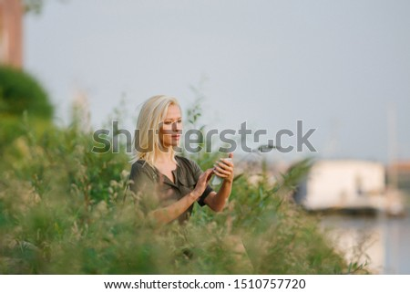 Portrait of a beautiful, slim and attractive middle-aged white woman (platinum blond European lady) in a casual green dress checking her smartphone as she sits on the grass a park at sunrise.