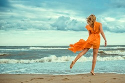 Portrait of a beautiful slim blond woman in orange mini dress with flying train dancing barefoot on the wet sand at the storming sea. Raging nature. Copy-space. Outdoor shot