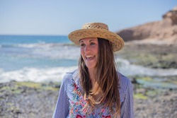 portrait of a beautiful smiling girl at the beach, wearing a flowery shirt and a summer hat