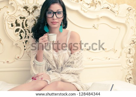 Portrait of a beautiful smiling girl in trendy glasses drinking tea or coffee in her vintage bedroom. Cup of hot beverage. Indoor shot