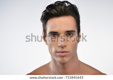 Portrait of a beautiful smiling man showing white teeth looking into camera or making faces of doubt or blunders with perfect skin and combed hair.