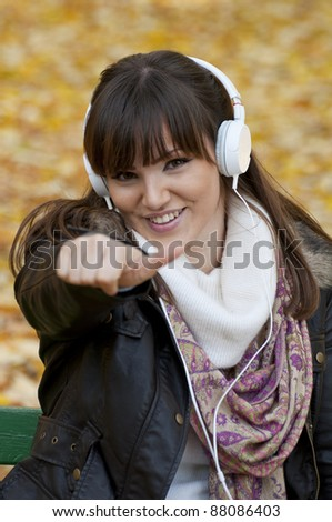 Portrait of a beautiful smiling woman listening to music with thumb up