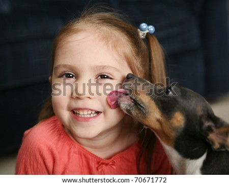 Portrait of a beautiful smiling young girl being licked on the cheek by a cute terrier puppy dog