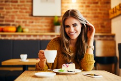 Portrait of a beautiful smiling young lady drinking coffee and looking at camera while sitting at table in a cafe
