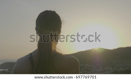 Portrait of a beautiful sportswoman in sportswear, feels happy, listens to music on the phone, background of a dark sunset. Concept: to love sports, run, burn calories, freedom, summer time, sun. #697769701