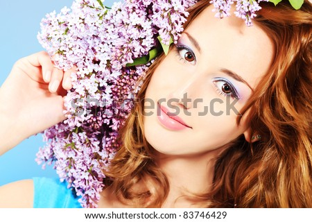 Portrait of a beautiful spring girl in lilac flowers.