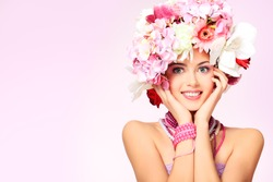 Portrait of a beautiful spring girl wearing flowers hat. Studio shot.