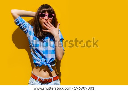portrait of a beautiful surprised girl in blue shirt and glasses on a background of orange wall