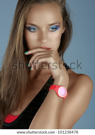 portrait of a beautiful tanned woman with dramatic eyeshadow and green manicure wearing pink neon watch