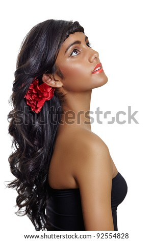 portrait of a beautiful tanned young woman with long brown curly hair and red flower, wearing red lipstick and black dress, sitting in profile on white background