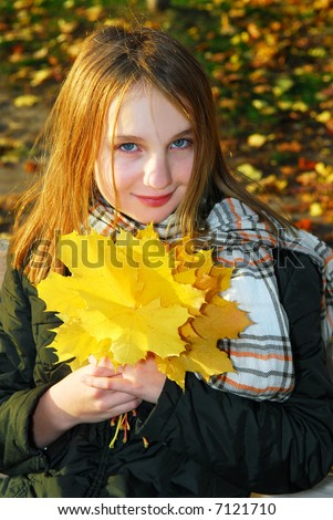 Portrait of a beautiful teenage girl with yellow fall maple leaves