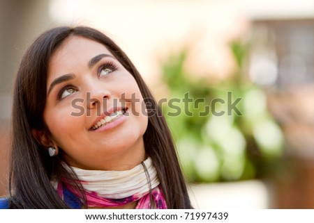 Portrait of a beautiful thoughtful woman smiling outdoors