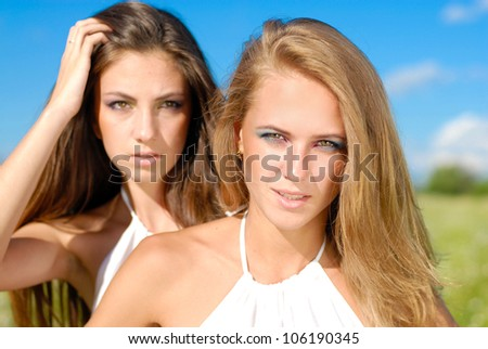 Portrait of a beautiful two happy young women with long hair and bright makeup outdoors on blue sky and field of green grass background