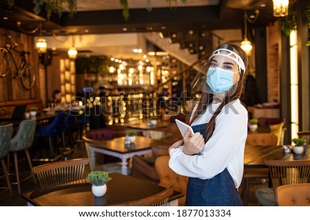 Portrait of a beautiful waitress working at a restaurant wearing a facemask to avoid the spread of coronavirus. COVID-19 lifestyle concepts. Ready for safe reopening during coronavirus epidemic!