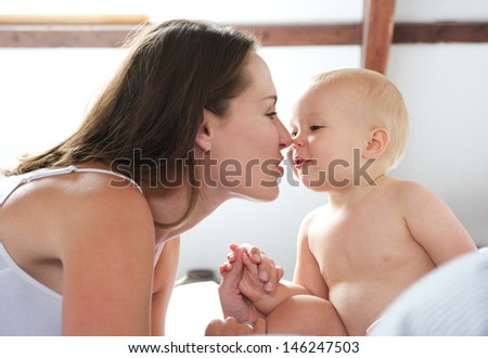 Portrait of a beautiful woman and baby playing on bed - stock photo