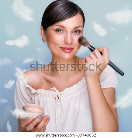 Portrait of a Beautiful woman applying makeup with brush on her face looking at camera and smiling against grey background. Feathers falls around her. Soft tender skin concept